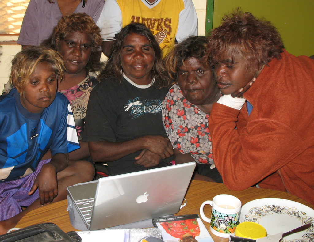 Marlene Nampitjinpa (center) with some relatives watching some of Dunlop's footage on a laptop at Kintore, 2006.